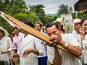 29 JUNE 2014 - DAN SAI, LOEI, THAILAND: A man plays a khaen (a bamboo flute from northern Thailand and Laos) during a merit making procession on the last day of the Ghost Festival in Dan Sai.  Phi Ta Khon (also spelled Pee Ta Khon) is the Ghost Festival. Over three days, the town's residents invite protection from Phra U-pakut, the spirit that lives in the Mun River, which runs through Dan Sai. People in the town and surrounding villages wear costumes made of patchwork and ornate masks and are thought be ghosts who were awoken from the dead when Vessantra Jataka (one of the Buddhas) came out of the forest. On the last day of the festival people participate in merit making ceremonies at the Wat Ponchai in Dan Sai and lead processions through town soliciting donations for the temple.    PHOTO BY JACK KURTZ