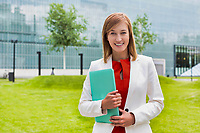 Portrait of young attractive businesswoman standing while holding document