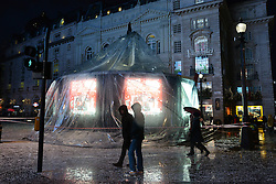 © Licensed to London News Pictures.23/12/2013. London, UK. The deflated globe covers the famous fountain. The Eros snow globe in Piccadilly Circus London today, 23rd December 2013,  after it was damaged by high winds and heavy rain. Photo credit : Peter Kollanyi/LNP