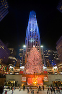 Skaters at Rockefeller Center Ice Rink, Christmas Tree and projected Snow Flakes on illuminated buildings.