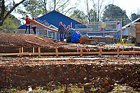 NC State DASA and facilities staff members carry siding to the townhouses under construciton at the Build-A-Block Habitat for Humanity project.