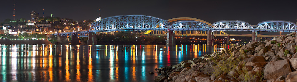 The L & N Pedestrian bridge and the Daniel Carter Beard bridge shimmer on the Ohio River at night, as seen from the Kentucky side.