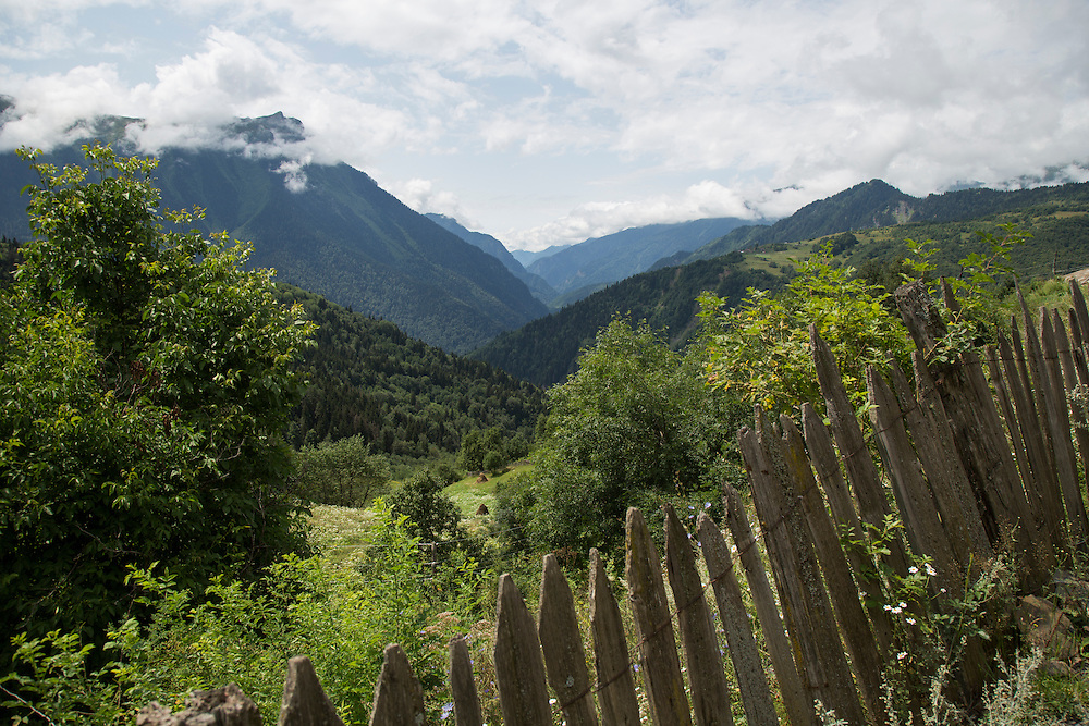 An old fence separates a jeep track up to Valery Vipliani's ramshackle house in the village of Kichhuldashi, from a field overgrown with wildflowers. Many villagers have moved to cities and towns because of a lack of opportunity. The Transcaucasian Trail hopes to change that by bringing tourists into the region. Below, the main valley of the Svaneti stretches out.