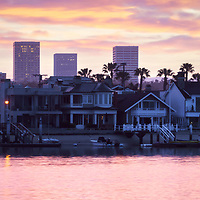 Newport Beach skyine sunrise panorama photo with Balboa Island homes, Newport Harbor, and Fashion Island office buildings. Newport Beach is an affluent beach city in Orange County Southern California in the United States of America. Panorama photo ratio is 1:3. Copyright ⓒ 2017 Paul Velgos with All Rights Reserved.