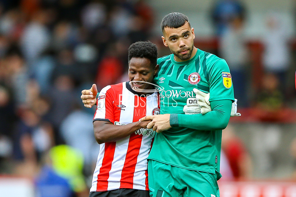 Brentford goalkeeper David Raya Martin (1) and Brentford midfielder Joel Valencia Castillo (16)  celebrate at the end of the match during the EFL Sky Bet Championship match between Brentford and Derby County at Griffin Park, London, England on 31 August 2019.