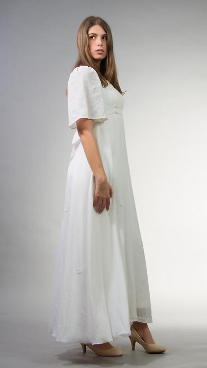 Female model posing in a white dress.