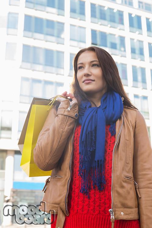 Thoughtful woman carrying shopping bags in winter
