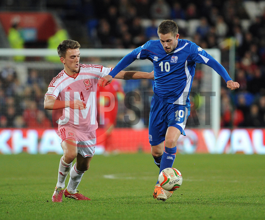 Gylfi Thor Sigurdsson (Tottenham Hotspur) of Iceland is closed down by Emyr Huws making his first cap for Wales (Manchester City) - Photo mandatory by-line: Dougie Allward/JMP - Tel: Mobile: 07966 386802 03/03/2014 -