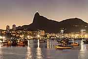 Christ the Redeemer statue is lighted at twilight across seen from across Guanabara Bay at the Urca neighborhood in Rio de Janeiro, Brazil.