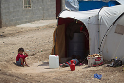 © Licensed to London News Pictures. 12/05/2013. Dohuk, Iraq. A young Syrian refugee sits outside his tent at the Domiz refugee camp in Iraqi-Kurdistan, set up for those escaping the ongoing civil war in Syria. The camp, close to the city of Dohuk, now houses in the region of 45,000 refugees, with around 400 new arrivals every day. Photo credit: Matt Cetti-Roberts/LNP