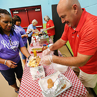 """Cancer survivor Wanda K. Gray is served a fried green tomato by Keith Jackson, of the Southern Motion Relay for Life Team, during the Relay for Life """"Give Cancer the Boot"""" event Friday night at Parkway Elementary School in Tupelo. The Lee County Relay for Life is an annual team fundraising event that benefits the American Cancer Society. This years theme was Give Cancer the Boot."""