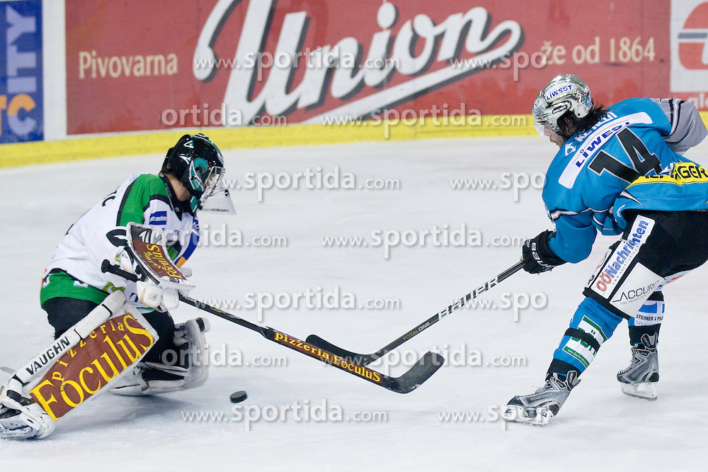 Goalie Matija Pintaric (HDD Tilia Olimpija, #69) stops Justin Keller (EHC Liwest Black Wings, #14) breakaway with poke check during ice-hockey match between HDD Tilia Olimpija and EHC Liwest Black Wings Linz in 37th Round of EBEL league, on Januar 9, 2011 at Hala Tivoli, Ljubljana, Slovenia. (Photo By Matic Klansek Velej / Sportida.com)