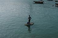 Hong Kong. fishermen in Shue wan Lama Island    Lama Island       /  pêcheurs à Shue Wan   /  Lama island: Des pêcheurs qui marchent sur l'eau.   /  Pour rejoindre les jonques ou ils habitent, les pêcheurs de lama ont inventé un moyen de transport bon marché, une planche en plastique  qui les amènent au rivage en tirant sur une ficelle.  Lama Island   village sur pilotis   /  R94/22    L1038  /  R00094  /  P0001932
