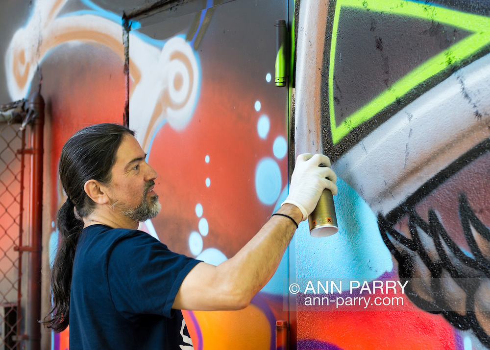"""Huntington, New York, U.S. 24th August 2013. SONIC BAD, legendary street artist JESSE RODRIGUEZ from the Bronx, is graffiti painting the """"Art Matters"""" wall, on the back of the Huntington Arts Council building, during the the art event """"Off the Walls"""" Block Party, by SPARKBOOM, a project the council created to help emerging artists, showcase talents, and help its artistic family network."""