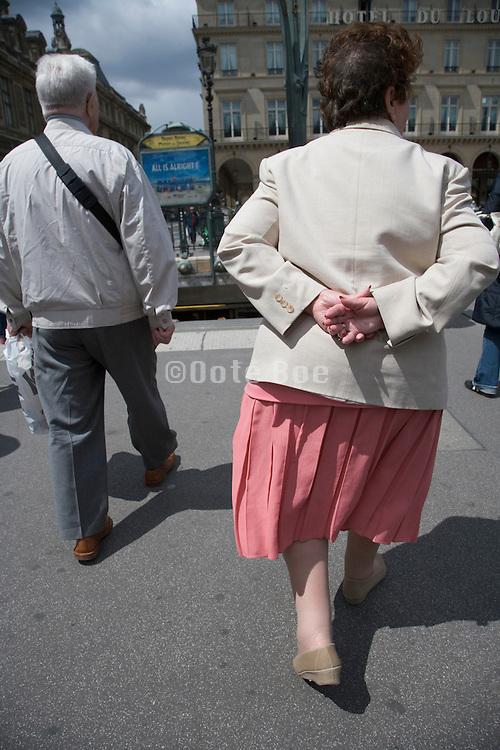 elderly tourist couple walking through Paris