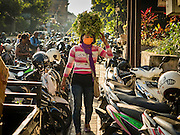 11 OCTOBER 2016 - UBUD, BALI, INDONESIA: A woman herbs on her hear down on Jalan (Street) Raya Ubud during the morning market. The morning market in Ubud is for produce and meat and serves local people from about 4:30 AM until about 7:30 AM. As the morning progresses the local vendors pack up and leave and vendors selling tourist curios move in. By about 8:30 AM the market is mostly a tourist market selling curios to tourists. Ubud is Bali's art and cultural center.      PHOTO BY JACK KURTZ