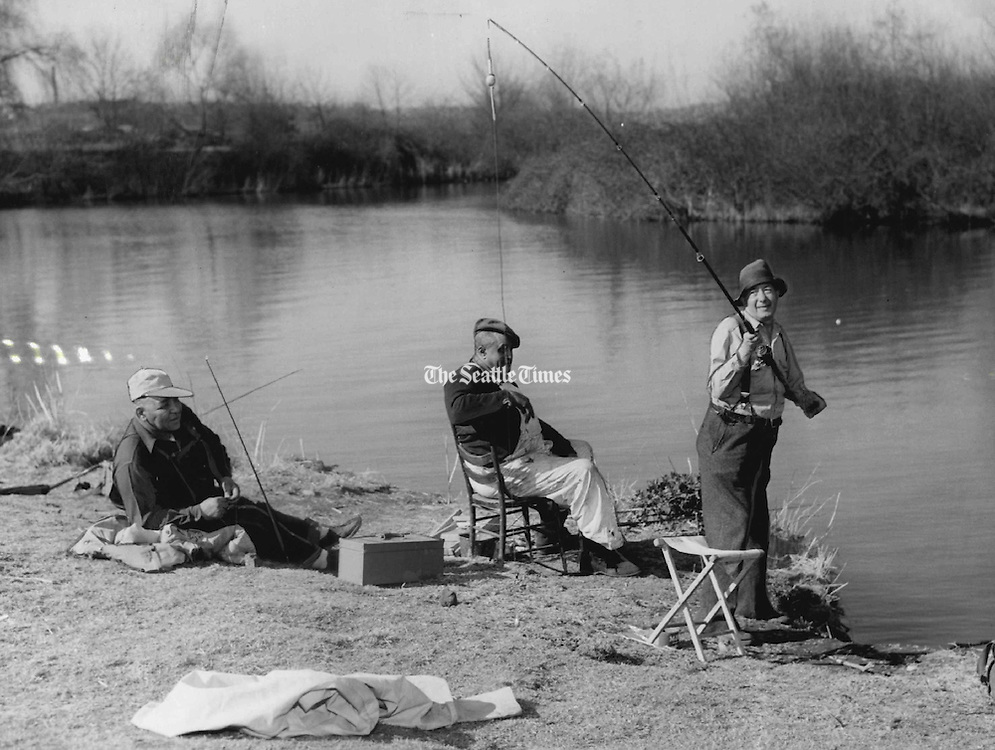 Spring Refuge: Superior Judge William G. Long, talking refuge from court affairs, prepared to fling his bait across a placid lake inlet bordering the University of Washington Arboretum yesterday. The jurist said he, like thousands of Seattleites, was lured outdoors by the warm spring weather. Watching were, from left, two other cat fishing fans, Carl Smith and Walter Derrick, who remarked: &quot;The judge has enough bait to catch a bear.&quot;<br /> (Vic Condiotty / The Seattle Times, 1955)