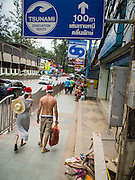26 DECEMBER 2014 - MAE KHAO, PHUKET, THAILAND: Tourists wearing Santa Claus hats walk under a tsunami evacuation sign on Patong beach in Phuket, Thailand. Nearly 5400 people died on Thailand's Andaman during the 2004 Indian Ocean Tsunami that was spawned by an undersea earthquake off the Indonesian coast on Dec 26, 2004. In Thailand, many of the dead were tourists from Europe. More than 250,000 people were killed throughout the region, from Thailand to Kenya. There are memorial services across the Thai Andaman coast this weekend.    PHOTO BY JACK KURTZ