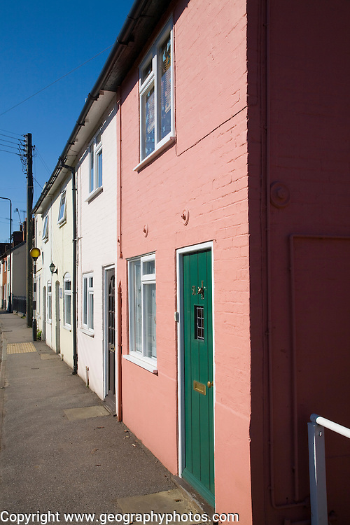 Row of small terraced houses opening onto pavement with no front garden, Melton, Suffolk, England