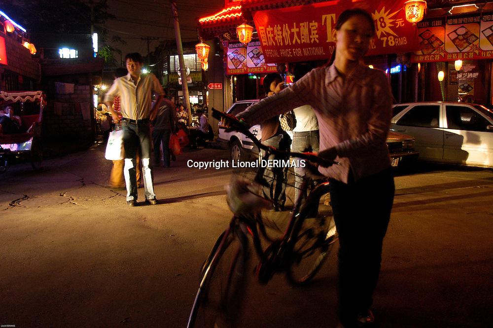 Woman and bike near Houhai lake, Beijing, China.