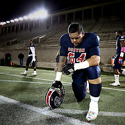Will Latu #64 of the Boston Brawlers kneels on the sideline prior to the first ever Boston Brawlers home game at Harvard Stadium on October 24, 2014 in Boston, Massachusetts. (Photo by Elan Kawesch)