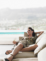 Woman reclining on sofa with champagne on balcony