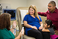 A healthcare worker discussing a sonogram with patients. Healthcare photography by Austin commercial photographer Matthew Lemke