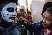 Una niña pinta de color negro las mejillas de un Xinacate durante el carnaval de San Nicolás de los Ranchos.