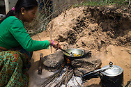 Kalpana Tamang (40), uses the kitchen utensils that was given to her in the 'Home-in-a-Box' as she cooks lunch outside her temporary shelter in Kavre, Bagmati, Nepal on 30 June 2015.  Kalpana, a widow with 3 children, has been supported by SOS Children's Villages for many years now and had receive the Home-in-a-Box after the earthquake destroyed her house, almost killing her two daughters. She now lives in a temporary shelter, sharing her dwelling with farm animals, and is trying to make ends meet by weaving bamboo baskets to supplement the financial assistance provided by SOS Childrens Villages. The NGO mostly supports her children's welfare and schooling as well as provides her with essential household and schooling items like kitchen utensils and school books and uniforms. Photo by Suzanne Lee for SOS Children's Villages