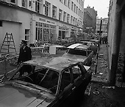 Car Bomb Damage in Dublin (E10)..1972.02.12.1972..12.02.1972..2nd December 1972..On the morning of 2nd December '72 two car bombs exploded in Dublin City. At Sackville Place two busmen were killed as they waited in their car to resume work. The busmen were named as George Bradshaw (30) and Thomas Duffy (23). The bomb was thought to be planted by a Northern Ireland subversive group who hoped to influence legislation going through Dail Eireann in relation to the I.R.A...Picture of a Garda surveying the damage around the corner from where the two Dublin busmen lost their lives in the explosion.