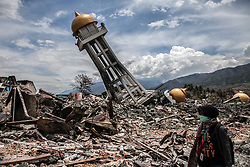 October 7, 2018 - Palu, Central Sulawesi, Indonesia - A resident searches for bodies under the ruin of a house in Balaroa, Central Sulawesi, Indonesia. A 7.5 magnitude earthquake rocked Central Sulawesi province on Sept. 28, triggering a tsunami and mudslides that killed a large number of people and displaced tens of thousands of others. Aid poured into disaster-ravaged Palu on October 7 after days of delays as efforts ramped up to reach 200,000 people in desperate need following a deadly quake-tsunami in the Indonesian city. (Credit Image: © Ivan Damanik/ZUMA Wire)