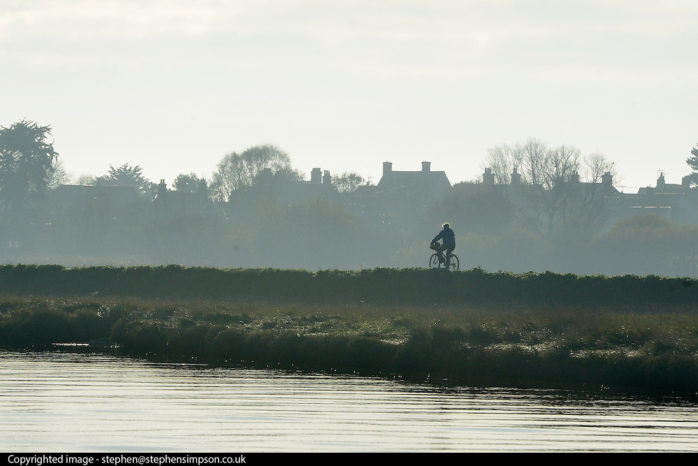 © Licensed to London News Pictures. 01/12/2013. Southwold, UK. A man cycles along a path. The first of December was greeted by a brisk sunny morning at the harbour on the River Blyth in Southwold, Suffolk today, 1st December 2013. Photo credit : Stephen Simpson/LNP