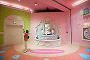 A woman takes a photo during  the opening of Hello Kitty's Kawaii (Cute) Paradise, a Hello Kitty theme store, in Tokyo, Japan on Thursday 21 October  2010. .Photographer: Robert Gilhooly