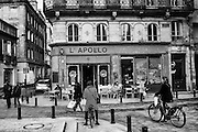 A woman in a polka dot coat stops briefly to text or email in front of L'Apollo in Bourdeaux, France.