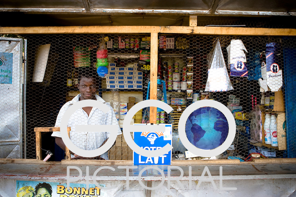 Ouagadougou, Burkina Faso, 4th September 2005.Boy behind chicken wire kiosk on Avenue Babban Guida, Ouagadougou.