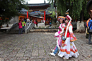 Tour guides in minority costume in Lijiang, Yunnan, China; September, 2013. The old town of Lijiang, once the capital of the Naxi kingdom, is now a popular destination for Chinese tourists.