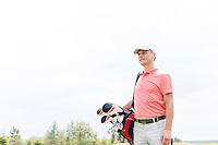Thoughtful middle-aged golfer looking away while carrying bag against clear sky
