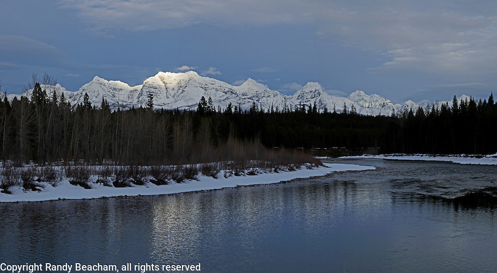 The Rocky Mountains in Glacier National Park and North Fork Flathead River at sunset in winter. Near Polebridge, Montana.