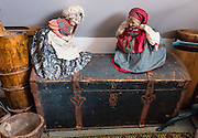 Female dolls in old-fashioned dress, aprons, and caps, stand on a trunk. Compass Rose Bed & Breakfast. Coupeville, Washington, USA. This fine 1890 Queen Anne Victorian home, on the National Register of Historic Places, is now an elegant two room bed and breakfast, furnished with antiques and glorious things from around the globe by the hosts, Captain and Mrs. Marshall Bronson.