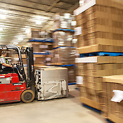 Forklift operator moving boxes in a distribution warehouse.<br />