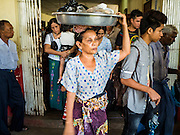 30 OCTOBER 2015 - YANGON, MYANMAR:  A vendor carrying her inventory on her head leaves the ferry terminal in Yangon to board the Dala ferry. The ferry to Dala runs continuously through the day between Yangon and Dala. Yangon, Myanmar (Rangoon, Burma). Yangon, with a population of over five million, continues to be the country's largest city and the most important commercial center.          PHOTO BY JACK KURTZ