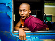 25 NOVEMBER 2017 - YANGON, MYANMAR: A Buddhist monk on the Yangon Circular Train. The Yangon Circular Train is a 45.9-kilometre (28.5 mi) 39-station two track loop system connects satellite towns and suburban areas to downtown. The train was built during the British colonial period, the second track was built in 1954. Trains currently run both directions (clockwise and counter-clockwise) around the city. The trains are the least expensive way to get across Yangon and they are very popular with Yangon's working class. About 100,000 people ride the train every day. A a ticket costs 200 Kyat (about .17¢ US) for the entire 28.5 mile loop.    PHOTO BY JACK KURTZ