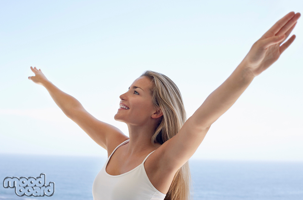 Young woman with arms outstretched on beach