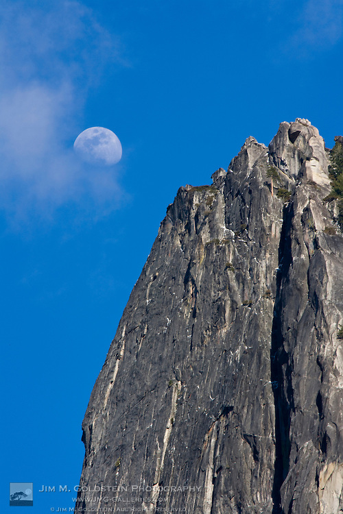 The moon rises and shines through the clouds above Cathedral Rock - Yosemite National Park, California