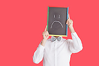 Man holding sad smiley face sign over red background