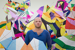 © Licensed to London News Pictures. 17/06/2013. London, UK. Brazilian artistMarcelo Jácome stands in his kite style sculpture 'Planos-pipas n17' (2013) at the press view for a new exhibition taking place at the West London based gallery. The exhibition, which runs from the 18th of June to the 29th of September 2013 at the Saatchi Gallery, is entitled 'Paper' and aims to challenge the viewers perceived ideas and expectations of the material in a world where its use is becoming rare thanks to emails and the internet  Photo credit: Matt Cetti-Roberts/LNP