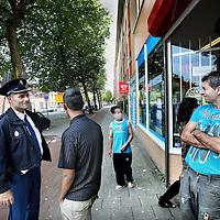 Nederland, Amsterdam , 25 augustus 2011..Standplaats Nieuw West..Buurtregisseur Rob Lasschuit maakt een praatje met enkele jongeren en de plaatselijke sigarenboer in Amsterdam Nieuw West..Foto:Jean-Pierre Jans