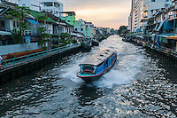 A water taxi travels down a canal at dusk in Bangkok, Thailand. The boat conductor stands on the side of the boat, collecting money from passengers inside.