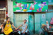 09 JULY 2011 - BANGKOK, THAILAND: Woman food vendors in front of a colorful wall in the Chinatown section of Bangkok, Thailand. Chinatown is the entrepreneurial hub of Bangkok, with thousands of family owned businesses selling wholesale merchandise in everything from food like rice, peanuts and meats, to dry goods like toys and shoes.  PHOTO BY JACK KURTZ