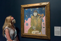 "© Licensed to London News Pictures. 04/08/2020. LONDON, UK. A staff member poses with ""Portrait of a Young Girl (Vaite 'Jeanne' Goupi')"", 1896, by Paul Gauguin.  Preview of ""Gauguin and the Impressionists : Masterpieces from the Ordrupgaard Collection"" at the Royal Academy of Arts in Piccadilly.  60 works from a collection of Impressionist paintings, assembled by wealthy Danish couple Wilhelm and Henny Hansen, are on show 7 August to 18 October 2020, and includes masterpieces by Gauguin, Degas, Monet, Morisot, Pissarro, Renoir and Sisley.  Photo credit: Stephen Chung/LNP"